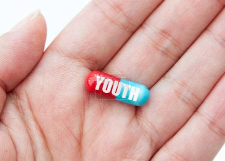 Photo for Hand holding a pill labelled with youth - Royalty Free Image