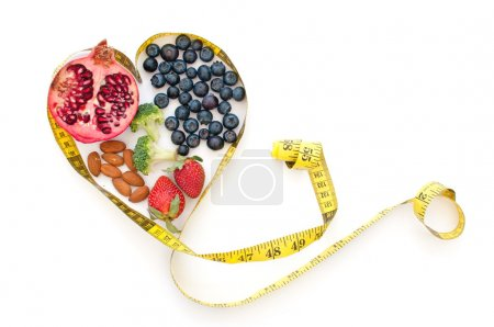 Photo for Superfoods such as pomegranate, blueberries and almonds inside a tape measure in the shape of a heart - Royalty Free Image