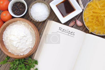 Photo for Open recipe book surrounded by cooking ingredients - Royalty Free Image