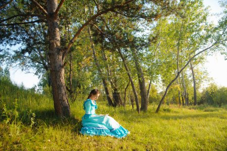 Photo for Woman in vintage dress reading a book while sitting under a tree - Royalty Free Image