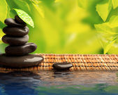 Green eco background with spa stones and leaves with water