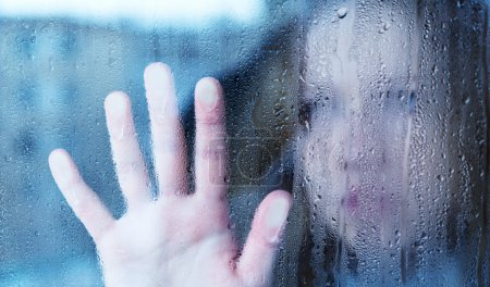 Photo for Hand of young woman melancholy and sad at the window in the rain - Royalty Free Image