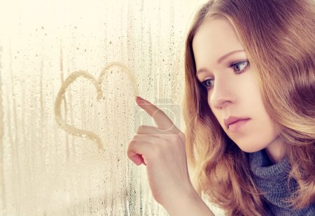 Photo for Sad enamored girl draws a heart on the window in the rain - Royalty Free Image