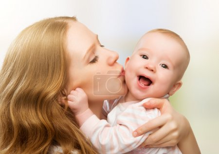 Happy cheerful family. Mother and baby kissing