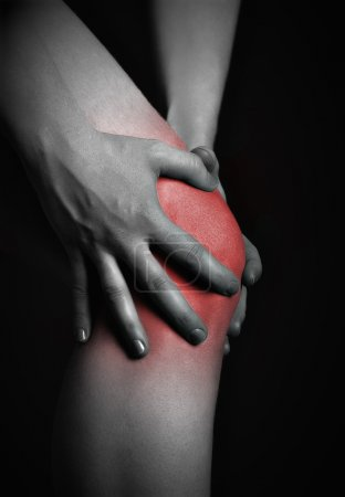 pain in the knee. Chiropractor doing massage in sick knee in red