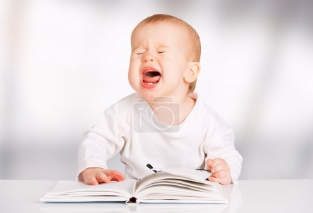 Funny baby with glasses reading a book and cries...