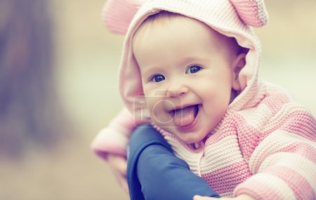 Photo for Happy smiling cheerful baby girl in pink hood with ears - Royalty Free Image