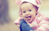 šťastné usměvavá holčička v růžových kapuce s ušima