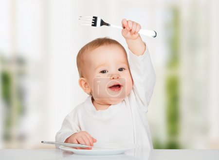 Funny baby with a knife and fork eating food