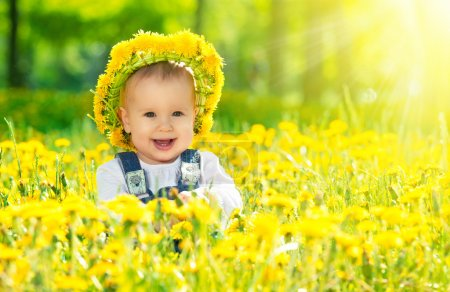 happy baby girl in a wreath on meadow with yellow flowers on t