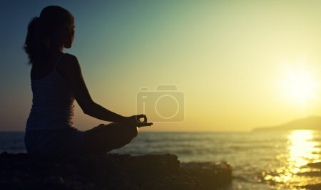 Photo for Yoga outdoors. silhouette of a woman sitting in a lotus position on the beach at sunset - Royalty Free Image