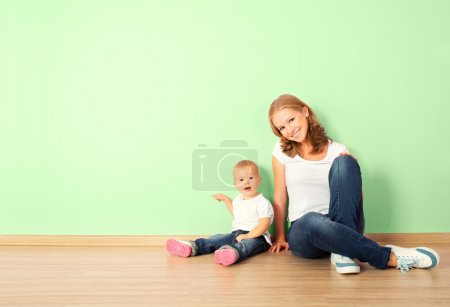 Photo for Happy family of mother and child is a toddler sitting on the floor in an empty home wall in the room - Royalty Free Image