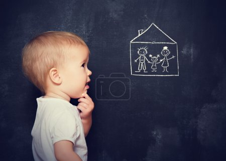 Concept baby looks at board, which is drawn family and home