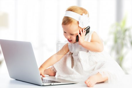 Photo for Baby girl with computer laptop and mobile phone - Royalty Free Image