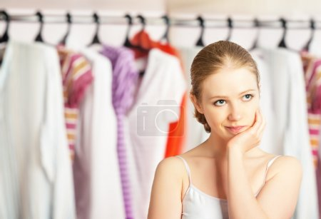 Photo for Young woman chooses clothes in the wardrobe closet at home - Royalty Free Image