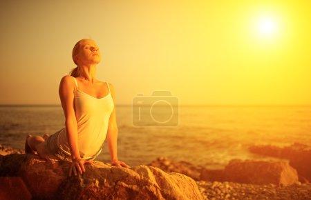 Photo pour Femme, faire du yoga sur la plage au bord de la mer au coucher du soleil - image libre de droit