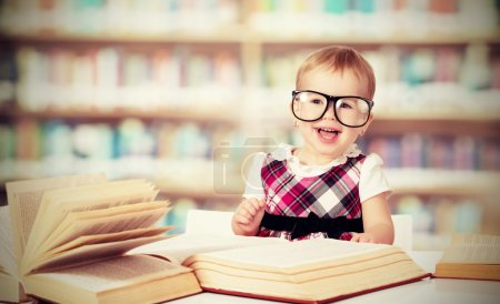 Photo for Funny baby girl in glasses reading a book in a library - Royalty Free Image