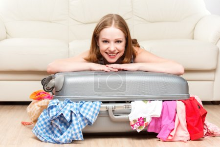 Photo for Happy woman is packing a suitcase at home - Royalty Free Image