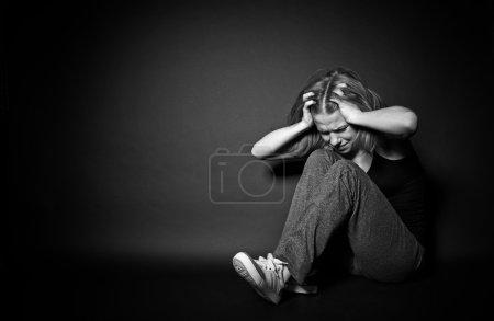 Photo pour Femme triste dans la dépression et le désespoir, pleurant serrant ses mains derrière sa tête sur un fond foncé noir - image libre de droit