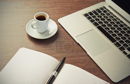 Foto de Escritorio de oficina con una taza de café ordenador portátil, cuaderno, pluma - Imagen libre de derechos
