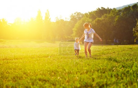 Photo for Happy family on nature walks in the summer. mother and child run on field - Royalty Free Image