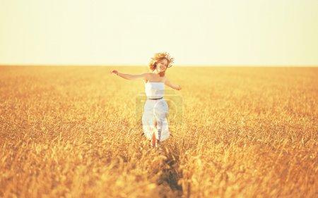 Happy young woman enjoying life in golden wheat field