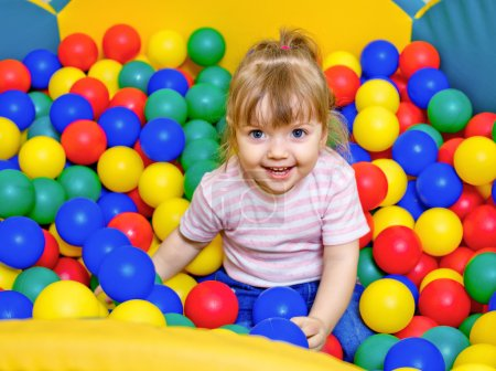 little girl playing in the pool balls