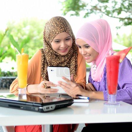 Photo pour Jeune femme musulmane asiatique en foulard avec ordinateur portable mobile - image libre de droit
