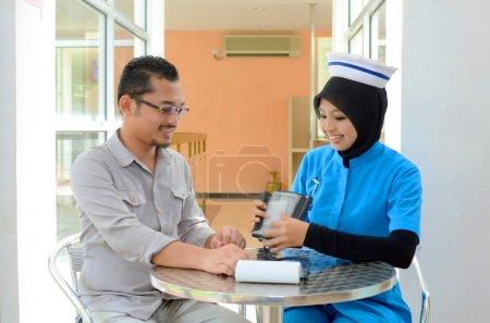 Photo pour Patient musulman confiant vérifiant la pression artérielle par infirmière - image libre de droit
