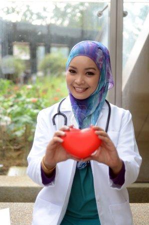 Photo pour Jeune asiatique musulmane femme médecin en tête écharpe sourire tout en tenant cas d'amour - image libre de droit
