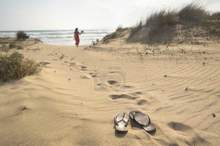 Photo pour Une belle femme marche pieds nus à travers les dunes de sable vers la mer laissant ses tongs derrière elle - image libre de droit