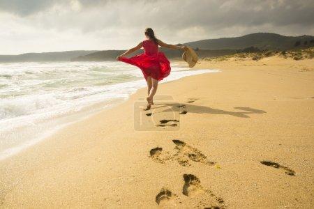 Photo pour Belle femme heureuse fonctionnant librement sur la plage - image libre de droit