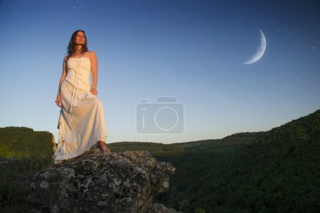 Photo for Beautiful young woman wearing elegant white dress standing on a rock overlooking the great expance of forests and mountains under blue sky with moon and stars - Royalty Free Image