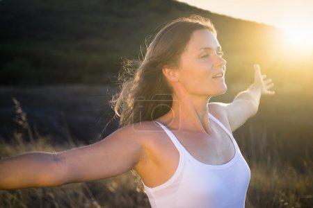 Photo pour Belle jeune femme, qui s'étend ses bras joyeusement louant la beauté de la vie. - image libre de droit