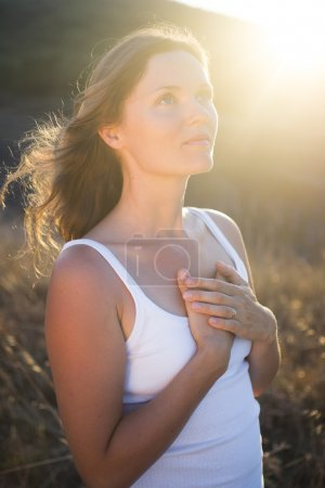 Photo for Beautiful young woman with her hands on her chest looking gratefully towards the sky. - Royalty Free Image