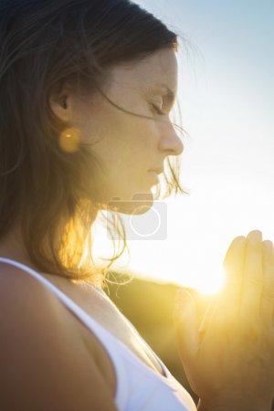 Photo pour Belle jeune femme en méditation silencieuse et prière connectée dans l'esprit avec l'amour universel de Dieu . - image libre de droit