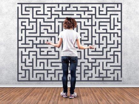 Photo pour Photo de la fille devant un mur avec un labyrinthe - image libre de droit