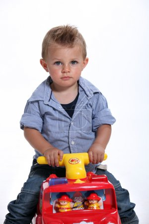 Young boy riding a toy fire engine