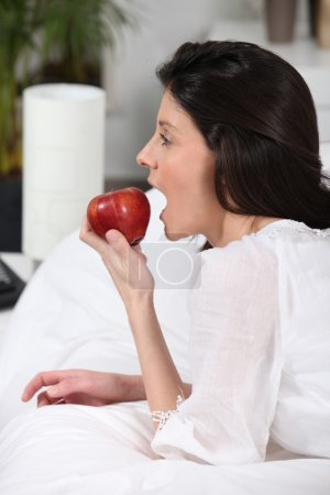 A woman eating an apple on a bed