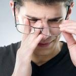 Young man rubs his eyes - eyesight problem concept...