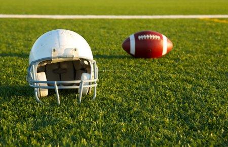 Football Helmet and Ball on the Field