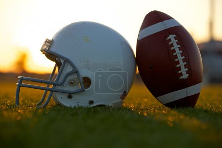 Football and Helmet on the Field at Sunset