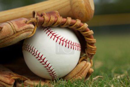 Photo pour Baseball dans un gant sur le terrain - image libre de droit