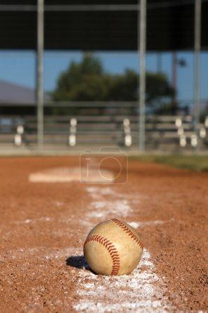 Photo pour Baseball sur champ avec gradins et base au loin - image libre de droit