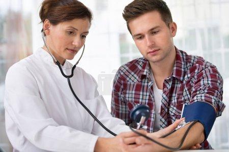 Photo pour Médecin féminin vérifiant la pression artérielle du jeune homme - image libre de droit