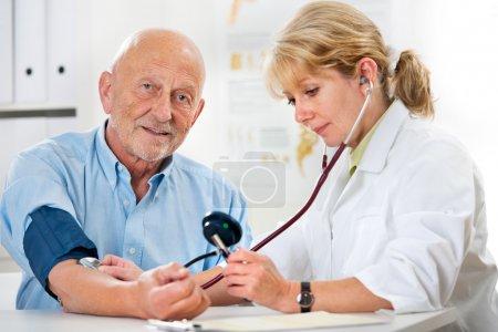Photo pour Femme médecin mesure la pression artérielle de l'homme âgé - image libre de droit