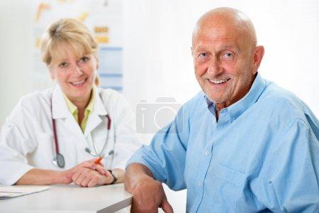 Foto de Paciente senior feliz y doctor en la oficina del médico - Imagen libre de derechos