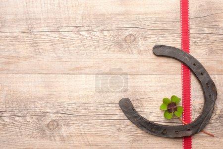 Photo pour Fers à cheval avec trèfle à quatre feuilles sur fond en bois - image libre de droit