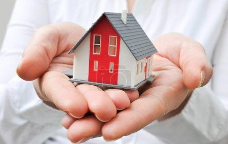 Photo pour Mains présentant une petite maquette d'une maison - image libre de droit