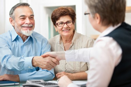 Photo for Senior couple smiling while shaking hand with financial advisor - Royalty Free Image